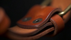 A beautiful brown belt with a metal buckle closeup macro Stock Footage