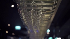 Group of empty wine glasses hanging from metal beams in a bar Stock Footage
