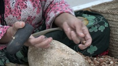 Woman cracking argan nuts in countryside workshop Morocco Stock Footage