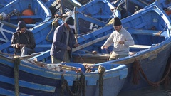 Fishermen at work in small harbor Essaouira Morroco Stock Footage