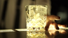 A glass of alcoholic beverage and ice cubes Stock Footage