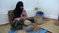 Muslim woman cracks argan nuts in workshop Morocco North Africa Stock Footage