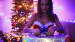 Young joyful beautiful woman opening the magical Christmas present. Girl sits Stock Footage