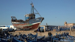 Wooden fishing boat repair in port Morocco North Africa Stock Footage
