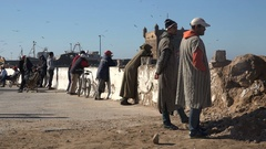 Locals look out over Atlantic Ocean in small town Essaouira Morocco Stock Footage
