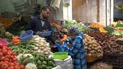 Veiled Muslim woman buys groceries at local market Morocco, North Africa Stock Footage