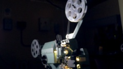Film projector. Old movie projector working in dark. Dolly shot Stock Footage