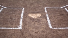 Home plate and a chain link fence at a little league baseball game. Stock Footage
