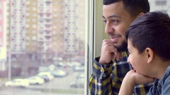 Father and son look out the window Stock Footage