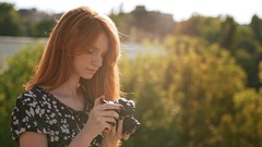 Smiling ginger girl in black and white dress shooting with film camera in Stock Footage