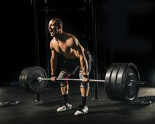 Man screaming while lifting heavy barbell in gymnasium Stock Photos