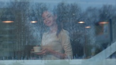 Young beautiful woman with a cup walking to her table in a cafe Stock Footage