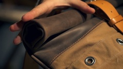 A man checking a new leather bag with leather belt and a metal buckle closeup Stock Footage
