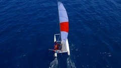 Aerial drone view of a man and woman sailing on a boat to a tropical island. Stock Footage