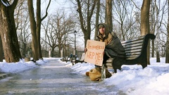 4K.Homeless young man with cardboard in  winter city park. Focus change Stock Footage