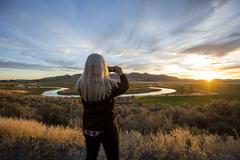 Caucasian woman photographing sunset over winding river Stock Photos
