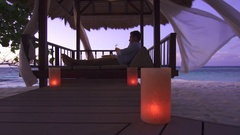 A couple drinking champagne on the beach at a tropical island resort hotel. Stock Footage