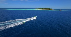 Aerial drone view of a man and woman on an inflatable tube towing behind a boat Stock Footage