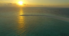 Aerial drone view of a man and woman eating dinner on a tropical island Stock Footage
