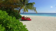A couple relaxing in chaise lounge chairs on the beach at a tropical island reso Stock Footage