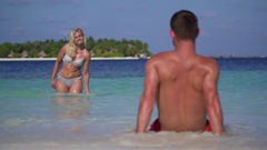 A playful woman splashes water on a man on the beach at a tropical island resort Stock Footage