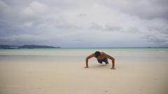 Man doing push-ups on the beach Stock Footage