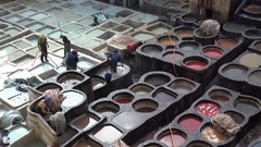 Workers of tannery dye animal skin by hand, manual labor in Fez, Morocco Stock Footage