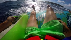 POV view of a man and woman on an inflatable tube towing behind a boat to a trop Stock Footage