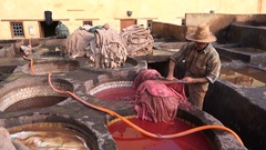 People at work in traditional outdoor tanneries in Fez Morocco Stock Footage