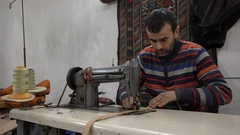 Moroccan man at work in leather workshop Fez Stock Footage