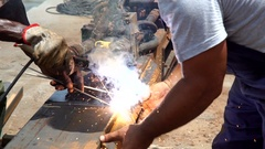 A man welds with a blowtorch a piece of metal. About industry Stock Footage