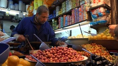 Shopowner sells olives and other food items in Fez Morocco Stock Footage