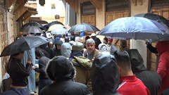 Men walk through the rain after Friday prayer in Fez, Morocco Stock Footage