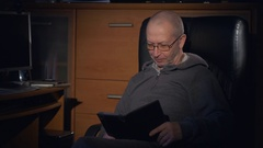 An elderly man in office chair at home with digital tablet and reading breaking Stock Footage