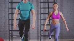 Men and women train together and doing sit-ups in the wall bars Stock Footage