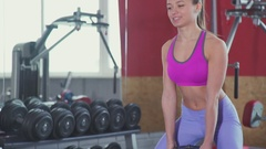 Athletic girl with an abdominal muscles perform squats with weighting Stock Footage