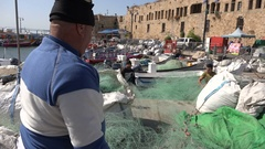 Israeli Arab fishermen sort their nets in port city Akko Stock Footage