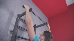 Athletic young man pulled on the bar in front of the wall Stock Footage