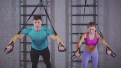 Fitness trainer and sport woman. Training in the wall bars: push-ups Stock Footage
