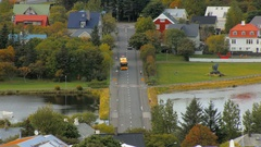 Bright yellow bus moves over bridge of lake Tjornin in Reykjavik in autumn time Stock Footage