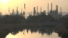 Smokestacks billow smoke from petrochemical facility at sunrise, Haifa Israel Stock Footage