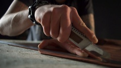 Craftsman with tattoos cutting leather with a sharp knife and a ruler Stock Footage