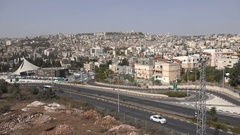 Traffic drives past Nazareth in Israel, with Basilica of Annunciation at center Stock Footage