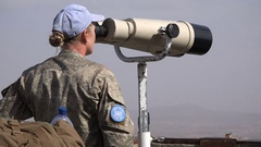 Female United Nations member uses binoculars to check Israel Syria border Stock Footage