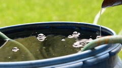 Rainwater streaming into the  barrel of water, zoom in Stock Footage