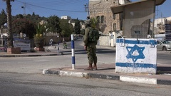 Israeli soldier guards Hebron settlement, Orthodox mother and child Stock Footage