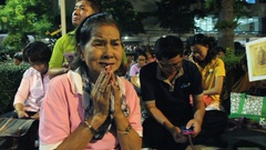 People react during prayers for Thai King Bhumibol Adulyadej's health. Stock Footage