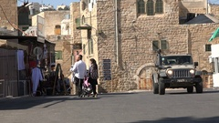 Jewish Orthodox settlers in Hebron, army patrol jeep drives by Stock Footage