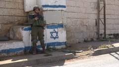 Young Israeli soldier, roadblock with national flag, Hebron West Bank Stock Footage