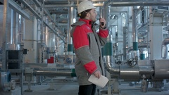 Engineer working in a thermal power plant with talking on the walkie-talkie for Stock Footage